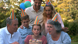 Happy family blowing the candles of birthday cake Footage