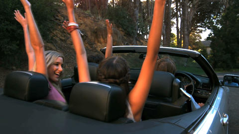 Friends raising their hands in the air while man is driving Live Action