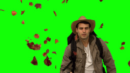 Man with a hat walking under leaves falling on green screen Footage