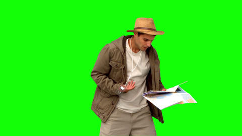Man with a map and a compass orienteering on green screen Footage