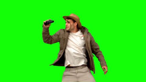 Man jumping and using binoculars on green screen Footage
