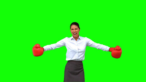 Determined businesswoman gesturing with boxing gloves on green screen Live Action