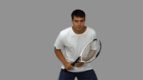 Handsome man training while playing tennis on grey screen Footage
