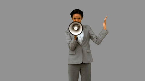 Businesswoman yelling into a megaphone on grey screen Footage