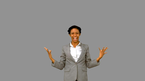 Pretty businesswoman raising arms on grey screen Live Action