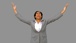 Angry businesswoman raising arms on grey screen Live Action