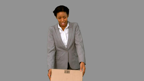Fired businesswoman dropping a box on grey screen Footage