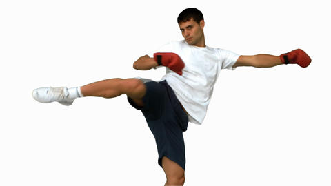 Boxer performing an air kick on white screen Live Action