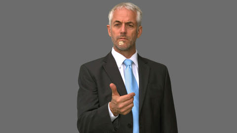 Elegant businessman throwing a dice in the air on grey screen Footage