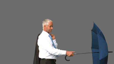 Businessman going under his umbrella on grey screen Live Action