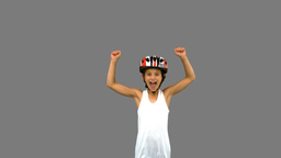 Cute girl wearing a bike helmet and raising arms on grey screen Live Action