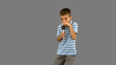 Little boy holding a microphone and singing on grey screen Footage