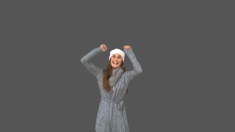 Cheerful young model in winter clothes jumping Footage