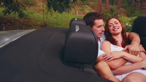 Beautiful couple embracing in a convertible car Footage