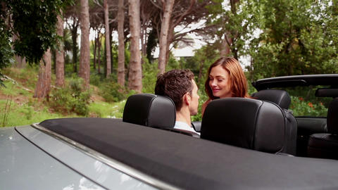 Beautiful young couple kissing in a convertible ca Footage