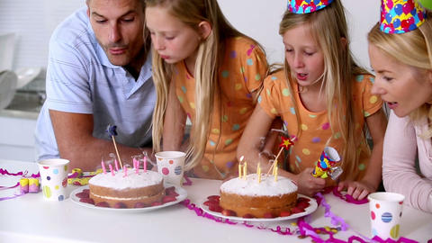 Twin sisters blowing out candles Footage