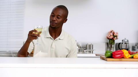 Man in kitchen drinking wine Footage