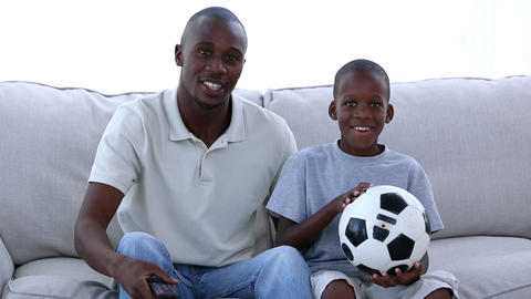 Father and his son watching football Footage