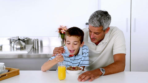 Father teasing son while he is having his breakfast Live Action