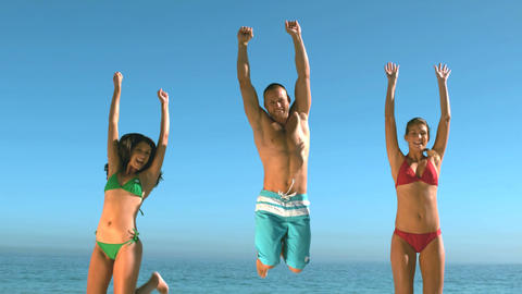 Attractive friends jumping on the beach at the sam Footage
