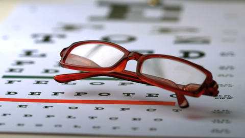 Reading glasses falling on an eye test Footage