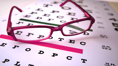 Pink reading glasses falling onto eye test Footage