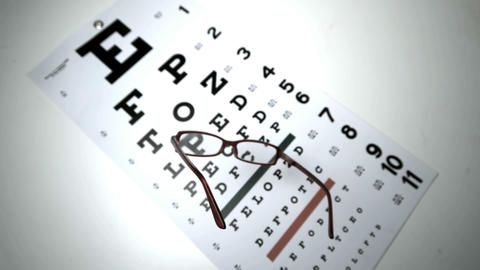 Black reading glasses falling onto eye test Footage