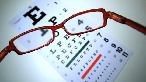 Red reading glasses falling on an eye test Footage