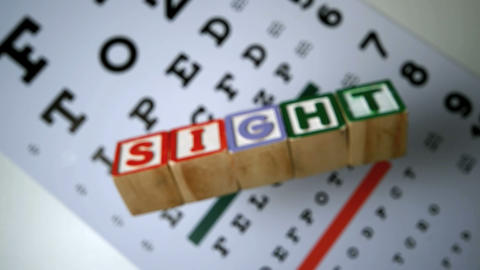 Blocks spelling out sight falling on eye test Footage