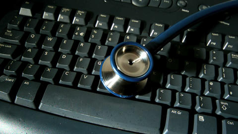 Stethoscope falling onto computer keyboard Live Action