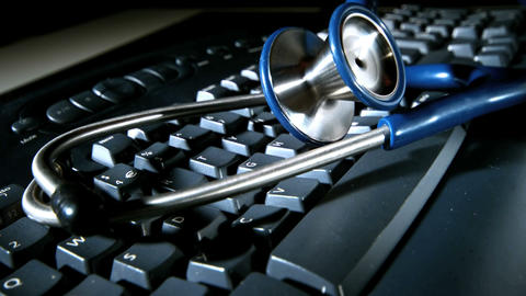 Blue stethoscope falling and bouncing onto computer keyboard Live Action