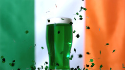 Shamrock confetti falling beside pint of green bee Footage
