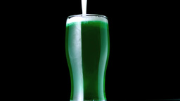 Foam falling into pint of green beer 影片素材