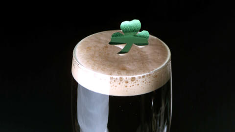Shamrock landing on head of pint of stout on black Filmmaterial