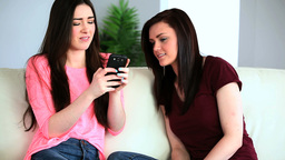 Brunette woman showing her smartphone to her frien Footage
