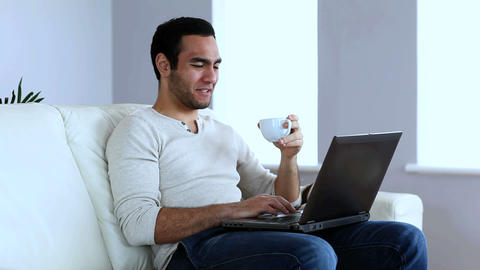 Man drinking a coffee while using a laptop Footage