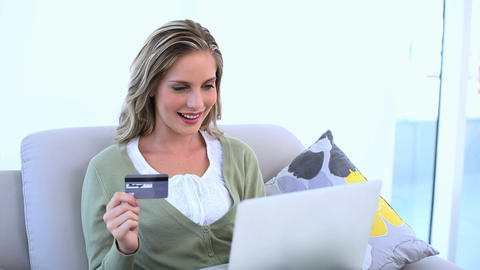 Delighted woman holding her credit card and using  Footage