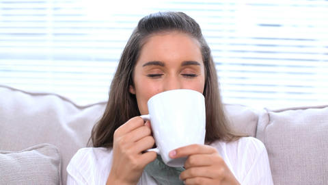 Smiling brunette sitting on sofa drinking her cup Footage