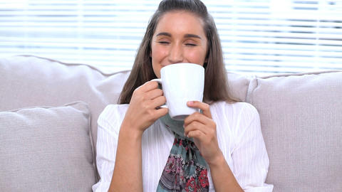 Brunette sitting on sofa drinking her cup Footage