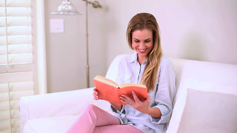Blonde woman reading book on sofa Footage