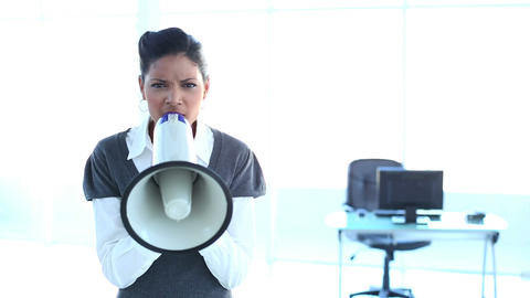 Serious businesswoman screaming in a megaphone Footage