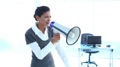 Furious businesswoman screaming in a megaphone Live Action