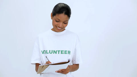 Smiling volunteer woman thinking and writting on n Footage