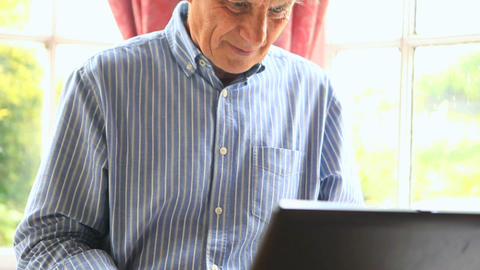 Focused mature man sitting by a window using his computer Footage