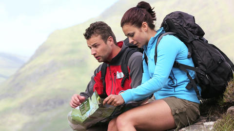 Lost couple sitting on a rock and consulting a map Footage
