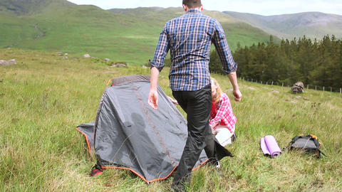Couple setting up their tent for the night Footage