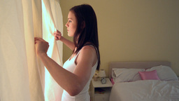 Young woman opening her bedroom curtains in the mo Footage