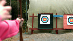 Woman shooting bow and arrow to the target Live Action