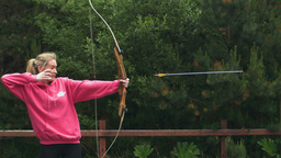 Blonde woman shooting bow and arrow Live Action