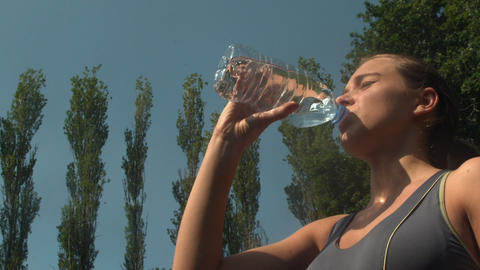 Athletic sporty woman drinking a bottle of water Live Action